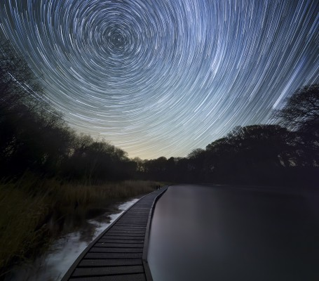 The Winter Stars spiral overhead in the Galloway Forest Dark Sky Park, Scotland. Foam churned up by November Storms floats downstream to Wigtown.