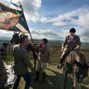 Horsemen, led by  Royal Burgh Standard Bearer Martin Rodgerson and his Burleymen attendants, arrive at the Three Brethren cairns summit, to check the boundaries of the lands, during the Common Riding festivities in Selkirk, in Selkirk, Scotland, Friday 14th June 2013.  From the book 'Unsullied And Untarnished, the Common Ridings of the Scottish Borders'.